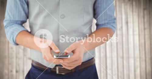 Man mid section with phone against blurry wood panel