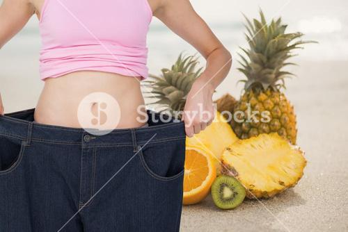Midsection of woman in loose jeans by pineapples representing weight loss