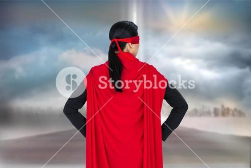 Rear view of business person wearing superhero cape against sky