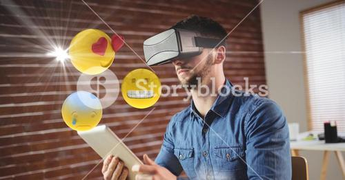 Man with VR glasses and digital tablet using emojis