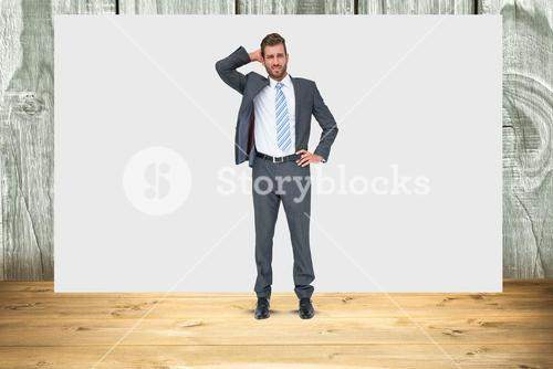 Confused businessman standing against blank sign