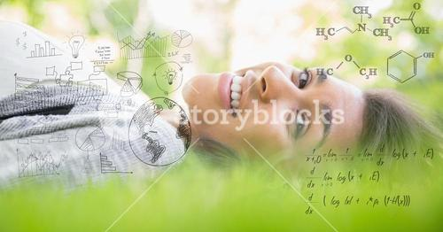 Digital composite image of happy woman lying on grass with equations