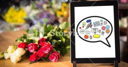 Various icons on digital tablet by flowers on table