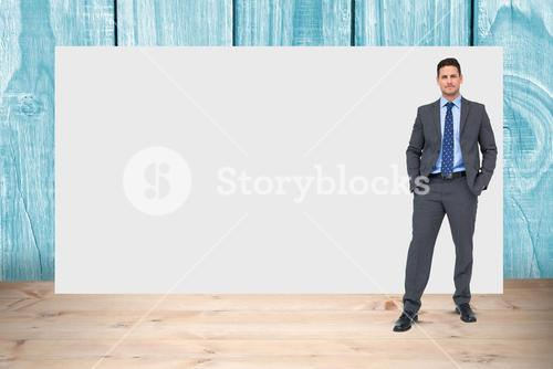 Portrait of confident businessman standing with hands in pockets against blank billboard