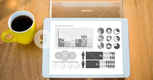 Various graphs on digital tablet by coffee cup at table