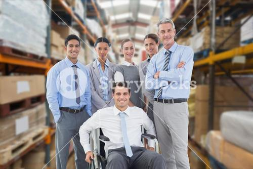 Portrait of smiling businessman in wheelchair with colleagues at warehouse