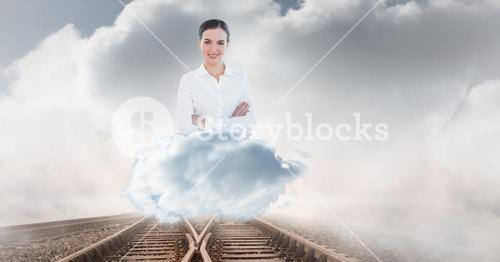 Digitally generated image of businesswoman on railroad track against cloudy sky