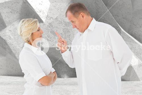 Senior man pointing at woman while arguing against gray background