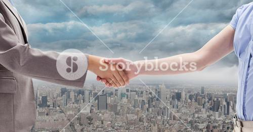Digitally generated image of  businesswomen doing handshake with city in background