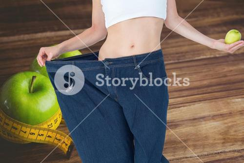 Midsection of woman in loose jeans holding  granny smith apple representing weight loss