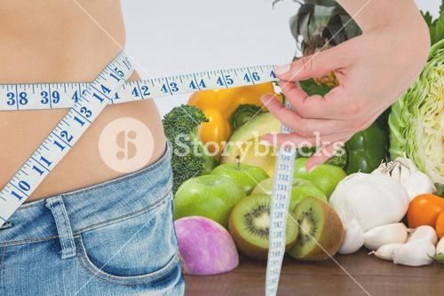 Midsection of woman measuring waist against fruits and vegetables representing weight loss