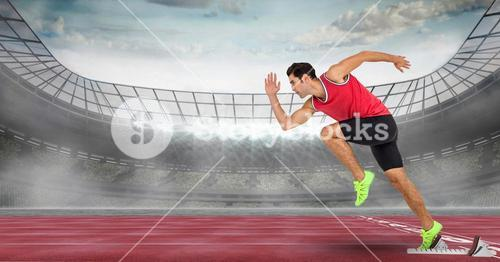 Side view of male athlete running from starting line at stadium