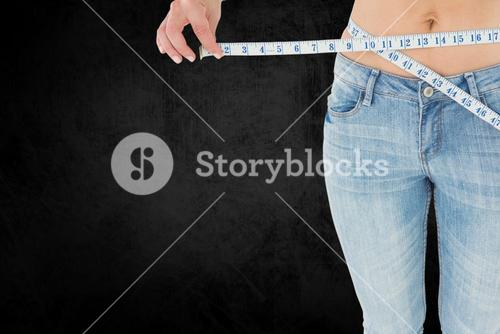 Midsection of woman measuring waist with tape measure representing weight loss