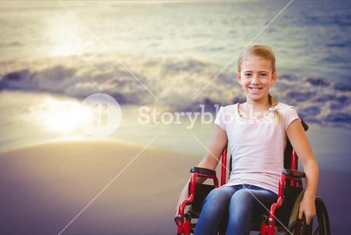 Portrait of smiling girl in wheelchair at beach
