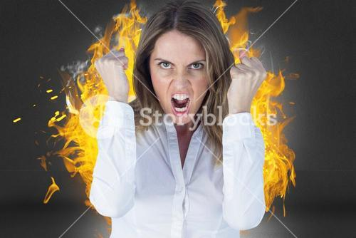 Digital composite image of angry businesswoman clenching fists against fire