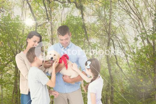 Happy family playing with dog in forest during summer