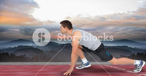 Side view of male athlete at starting line by sea against cloudy sky