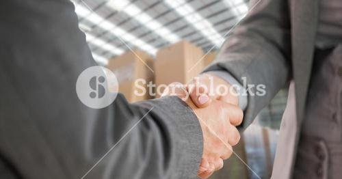 Close-up of business people shaking hands in warehouse
