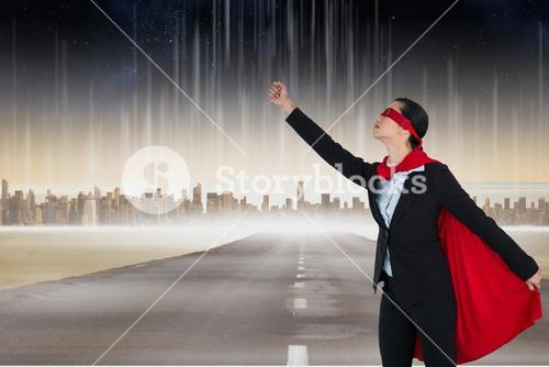 Digital composite of businesswoman in superhero costume on road in city
