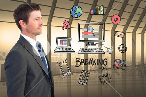 Businessman looking at various icons surrounding computer and breaking news