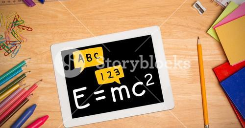 Directly above shot of formula in digital tablet with color pencils and school supplies on wooden ta