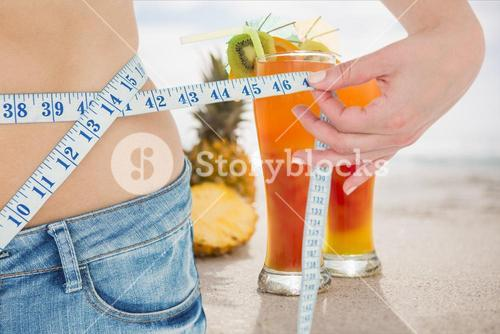 Midsection section of woman measuring waist with juices in background