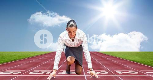 Businesswoman in starting position on tracks