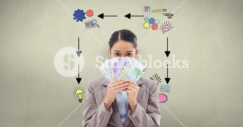 Businesswoman holding banknotes against signs on wall