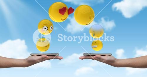 Digitally generated image of emojis flying over hands holding smart phone against sky