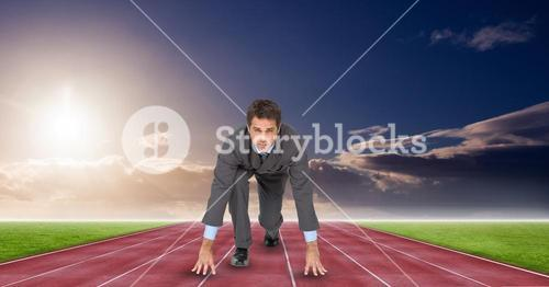 Businessman in starting position on tracks