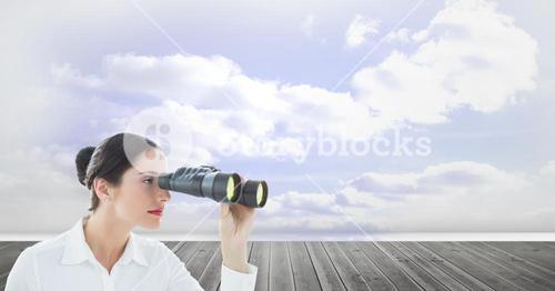 Businesswoman using binoculars against cloudy sky