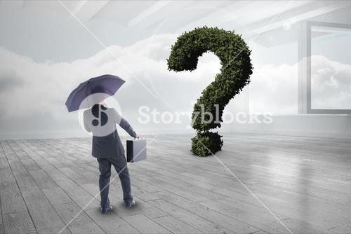 Businessman with umbrella and briefcase looking at question mark made of plants