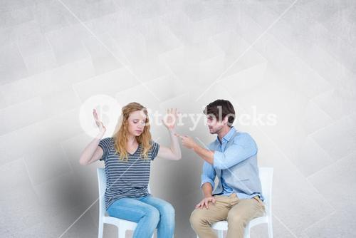Couple arguing while sitting on chairs
