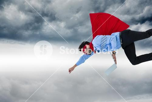 Businessman wearing super hero cape while holding laptop in sky