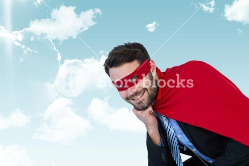Businessman wearing super hero costume in sky