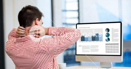 Tired businessman looking at graphs in desktop pc while working office