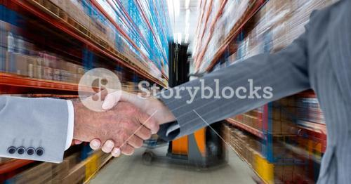 Cropped image of business people doing handshake in warehouse
