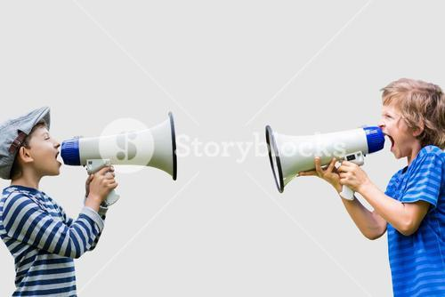 Boys shouting on megaphones while standing against gray background