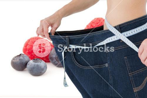 Midsetion of woman wearing loose jeans with fruits in background
