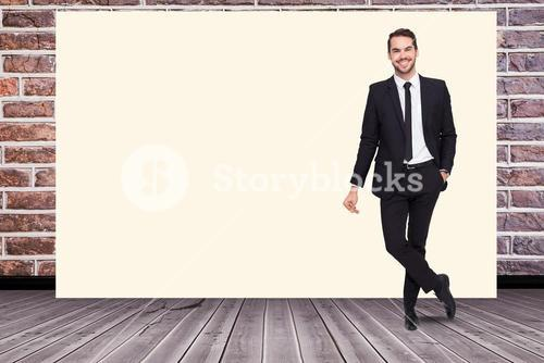 Portrait of smiling businessman standing by blank white billboard against brick wall