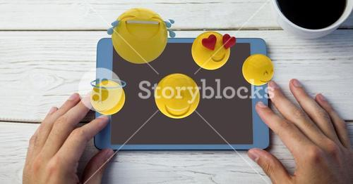 Digitally generated image of emojis flying over hands using digital tablet by coffee cup at table