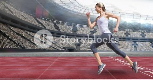Side view of female athlete running on racing track