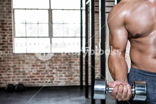 Midsection of man exercising with dumbbells at gym
