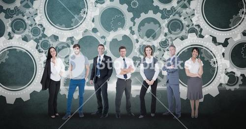 Digitally generated image of business people standing against gears in background
