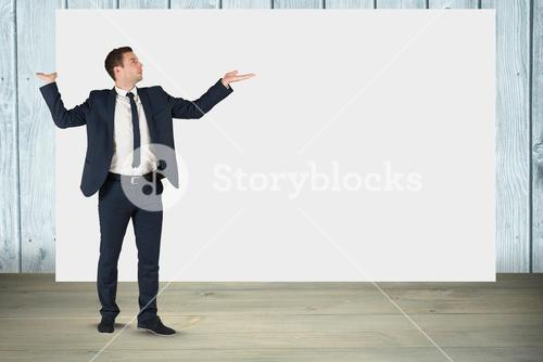 Businessman gesturing while standing against blank billboard