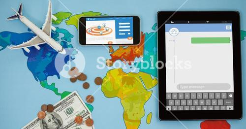 Overhead view of smart phone and tablet computer on world map with currency