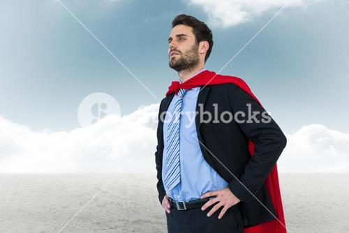 Businessman wearing cape while standing against sky