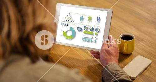 High angle view of businesswoman looking at graphs and chart in tablet computer while sitting by tab