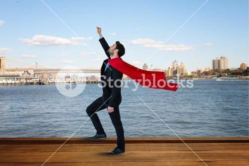 Side view of businessman wearing cape with arm raised standing by river against city
