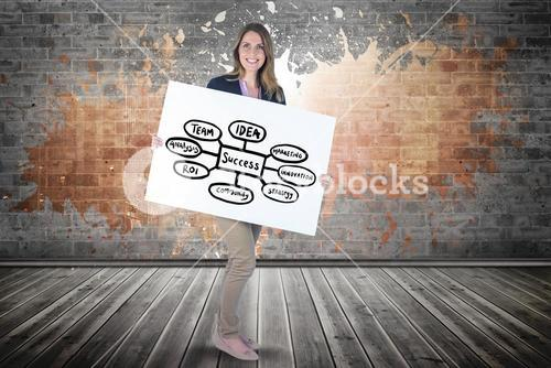 Smiling woman holding billboard with chart while standing against brick wall